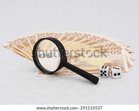 Real magnifying glass and euro notes with dice. Low angle and narrow depth of field for security and copyright reasons. Genuine magnification. - stock photo