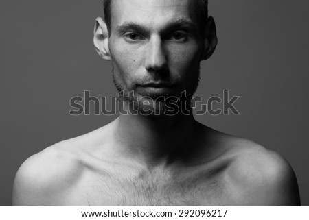 Real natural male beauty concept.Close up portrait of handsome charismatic man posing over gray background in black and white colors. Classic style. Black and white studio shot - stock photo