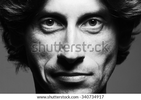 Real natural male beauty concept. Close up portrait of handsome charismatic man posing over gray background in black and white colors. Classic style. Black and white studio shot - stock photo
