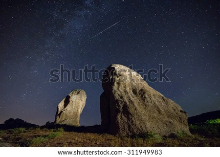Real night sky landscape with a perseid meteor and two menhirs - stock photo