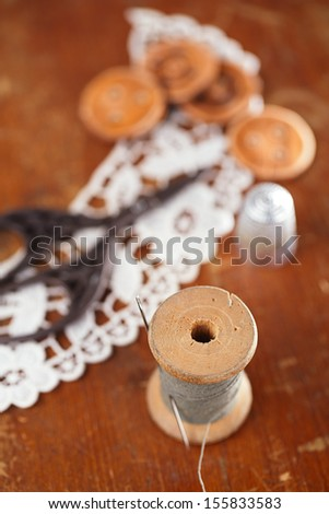 real old reels spool with color treads old wooded and  thimble and lace backdrop, shallow dof - stock photo