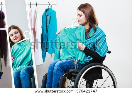Real people, disability and handicap concept. Teen girl handicapped woman sitting on wheelchair choosing clothes in wardrobe or  looking for some clothes in shop - stock photo