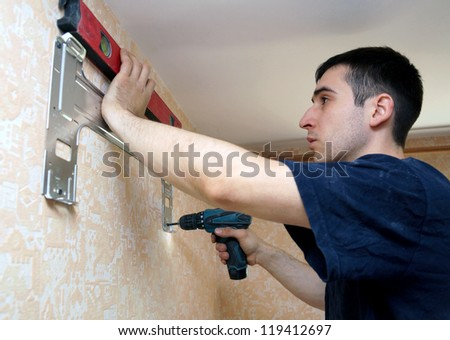 real photo of installation of the conditioner, fastening to a wall - stock photo