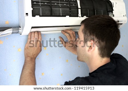 real photo of installation of the conditioner, the worker establishes the internal module - stock photo