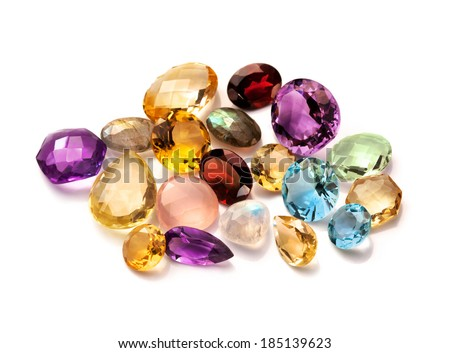Real polished gemstones  isolated on white background. Collection of different gems: red garnet, rose and lemon quartz, brazilian amethyst, citrine, blue topaz, moonstone rainbow and labradorite. - stock photo