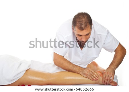 Real professional masseur giving therapeutic massage to woman's legs - stock photo