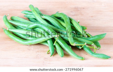 Realistic approach to food, imperfect green beans sheath over wooden cutting board. - stock photo