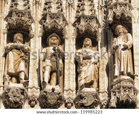 Realistic medieval gothic statues on facade of the historical City Hall on Grand Place in Brussels, Belgium in sunny day - stock photo
