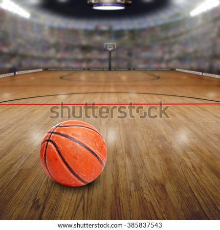 Realistic rendering of basketball arena full of fans in the stands with ball on court and copy space. Deliberate focus on seasoned basketball and shallow depth of field on background. - stock photo
