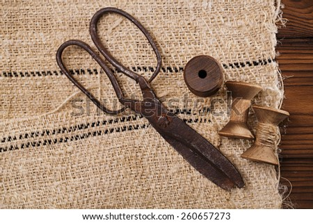 really antique iron scissors with spools on old grain sacking linen Completely hand made  handwoven and homespun - stock photo