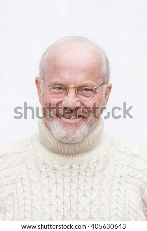 Really happy looking older man dressed in white knitted sweater looking into camera. - stock photo