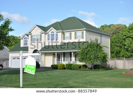 Realtor For Sale Sign on landscaped front yard lawn of large suburban home in residential neighborhood - stock photo