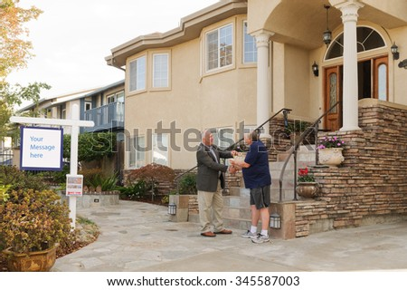 Realtor handing over keys to a house to the new home owner with blank sign with room for your text - stock photo