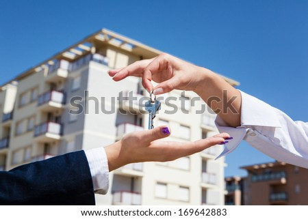 Realtor is giving the keys to an apartment to some clients, focus on the keys - stock photo