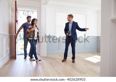 Realtor Showing Hispanic Couple Around New Home - stock photo