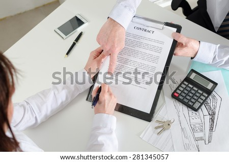 Realtor showing where to sign the real estate contract, top view - stock photo