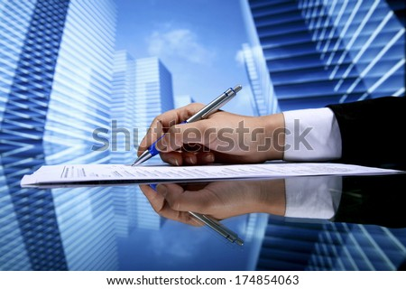 Realtor signing contract on skyscrapers background - stock photo