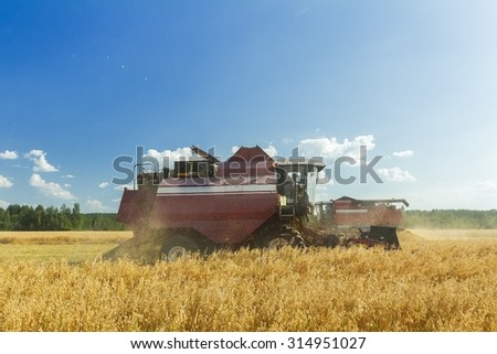 Reaping combine machine with reel and cutter bar in farm field  - stock photo