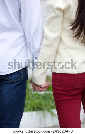 Rear close up angle boyfriend and girlfriend holding hands outdoors - stock photo