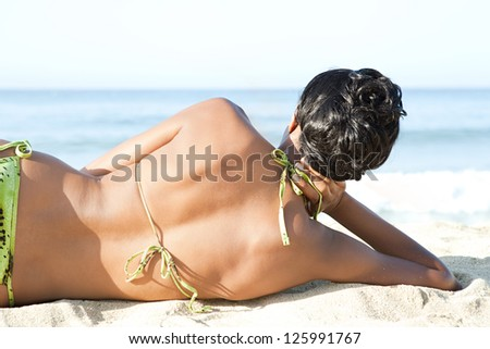 Rear close up view of a sexy black woman laying on a white sand beach contemplating the sea on a sunny day on vacations. - stock photo