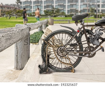 Rear end of dirty motorized bicycle chained to rusty metal bike rack in suburban park. Heavy chain through rear wheel. Motor attached to bike frame. Grass, people, buildings in background.  - stock photo