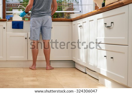 Rear low angle view of male in the kitchen doing household chores - stock photo
