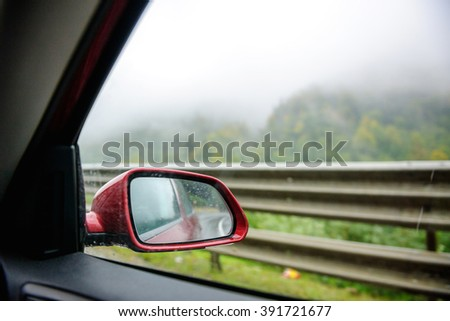 Rear mirror view with typical Iceland landscape - mist mixed with green vivid colors of the trees and rain - stock photo