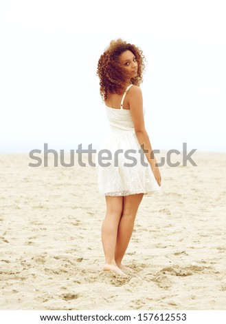 Rear portrait of a beautiful young walking on sand and looking over shoulder - stock photo