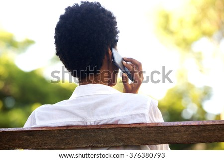 Rear portrait of young woman sitting on a park bench and talking on mobile phone - stock photo