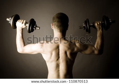 Rear shot of muscle man with two dumbbells - monochrome - stock photo