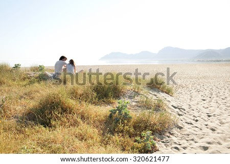 Rear side portrait of a young tourist couple sitting together in the distance on a white sand dunes beach  on a sunny day on holiday, outdoors. Travel and vacation lifestyle, nature living exterior. - stock photo