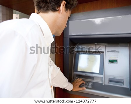 Rear side view of a businessman using an atm machine to withdraw money, outdoors. - stock photo