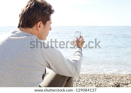 "Rear side view of a smart man sitting on a pebble beach on a sunny winter day, taking a photograph of the sea with his ""smart phone"". - stock photo"