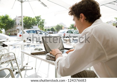 Rear side view of a young businessman using a laptop computer while sitting at a coffee shop terrace table under a parasol, outdoors. - stock photo