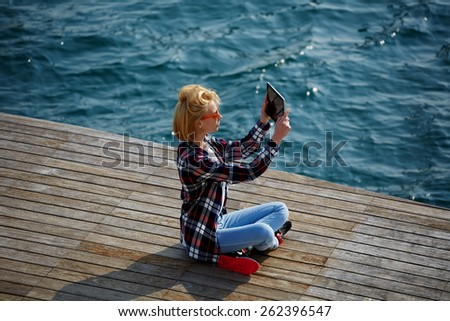 Rear top view of a young woman taking a picture of a view with her digital tablet while he sit on a wooden pier next to the sea, cute female tourist photographing view sitting against sea waves - stock photo