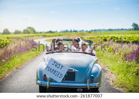 rear view, a newlywed couple is driving a retro car on a country road with their two beautiful children, they are looking at camera - stock photo