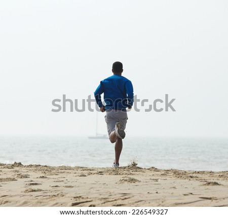 Rear view african american man jogging at the beach   - stock photo