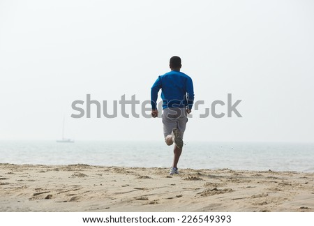 Rear view african american man running on the beach  - stock photo