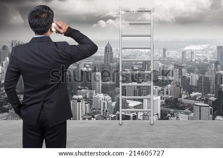 rear view business man in suit speaking by the phone against ladder going up in high sky against balcony overlooking city dusky before rain falling - stock photo