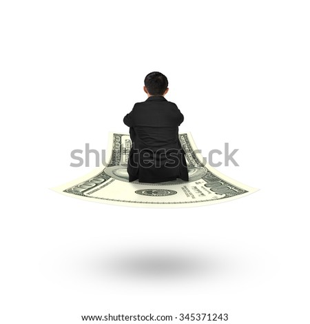 Rear view businessman sitting on money flying carpet, isolated on white background. - stock photo