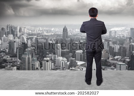 rear view businessman standing cross one's arm chest against balcony overlooking city dusky before rain falling - stock photo