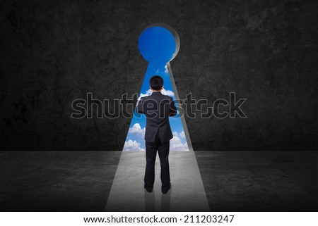 rear view businessman standing cross one's arm front of keyhole on old grunge black wall against blue sky background - stock photo