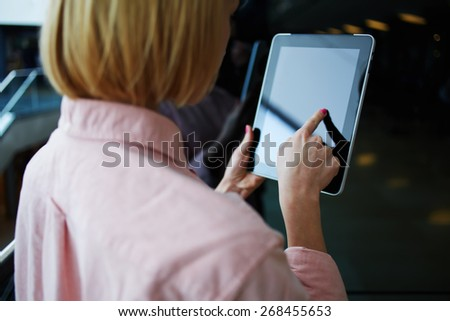 Rear view female person using digital tablet, business woman or freelancer working on touch pad in elevator, businesswoman using her wireless devices in modern office, young successful browsing on pad - stock photo