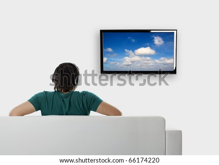 Rear view from a young man seated on the couch watching tv - stock photo