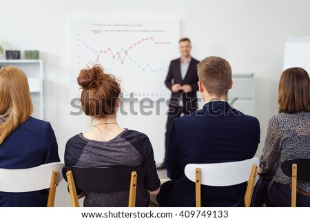Rear view from backs of people of out of focus team leader talking about charts on large white board during staff meeting - stock photo