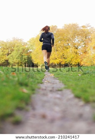Rear view image of young woman jogging in a park on a summer day. Fit and healthy female athlete exercise running in park - Outdoors - stock photo