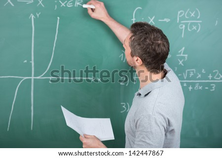Rear view mature male teacher holding paper while writing on chalkboard in classroom - stock photo