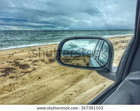 Rear view mirror on beach - stock photo
