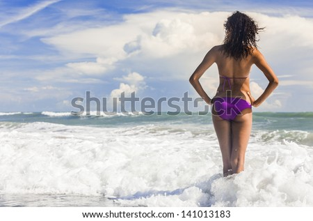 Rear view of a beautiful young woman in bikini standing in the surf waves on a deserted tropical beach with blue sky - stock photo