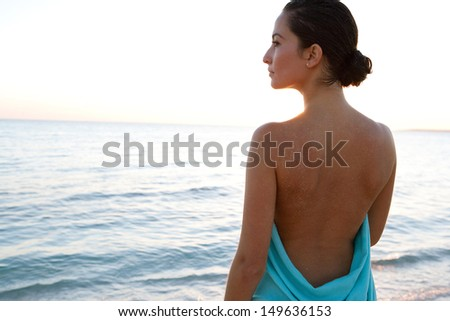 Rear view of a beautiful young woman standing by a calm sea and wearing a blue fabric sarong around her body, with bare shoulders and back. Elegant and ethereal. - stock photo